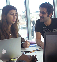 Two students sitting at a table with laptops on it in conversation.