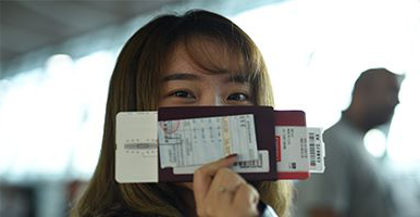 Woman holding a passport and tickets in front of her face