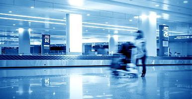 Long exposure shot of a person pushing luggage through an airport.